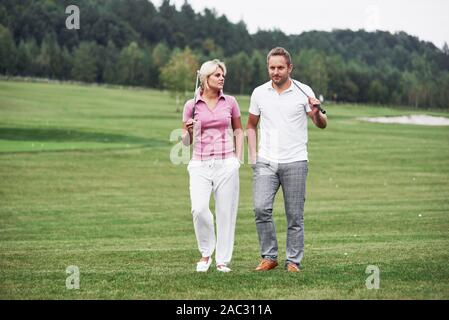 Couple of golf players with sticks in their hands walking on the lawn - Stock Photo