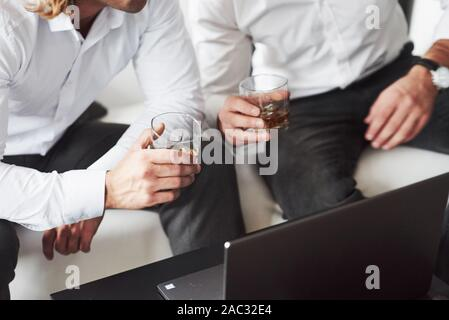 Particle view of the two businessmen sitting near the laptop and holding whiskey glass - Stock Photo