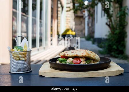 sandwich with chicken pieces, green salad and tomato, decorated with French fries and parsley leaves, black background - Stock Photo