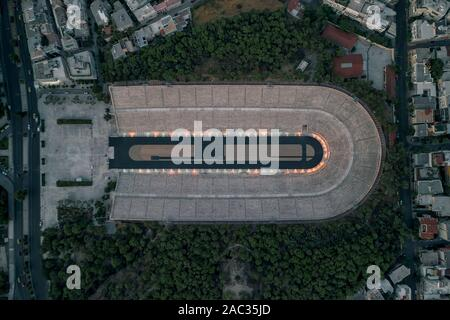 Overhead aerial drone shot of Panathenaic marble stadium with lights in dusk Pangrati, Athens - Stock Photo