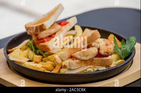 Chicken sandwich in toast bread, with French fries as a bowl, on a white background, restaurant, served - Stock Photo