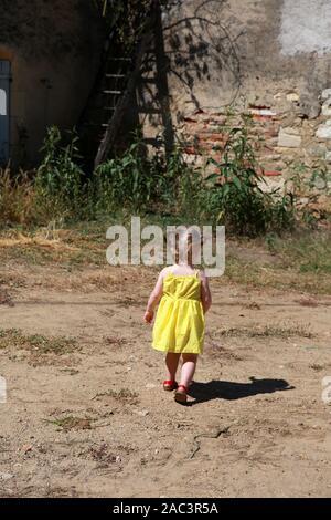 Toddler girl walking, back view. - Stock Photo