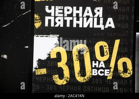 Moscow, Russia. 30th of November, 2019 An advertising poster with inscription in Russian 'Black Friday 30% discount on everything' during the annual sales action an entrance to a shop in the centre of Moscow city, Russia - Stock Photo