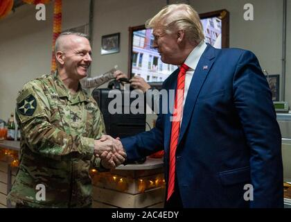 U.S. President Donald Trump shakes hands with Army Command Sgt. Maj. John W. Troxell, senior enlisted advisor to the chairman of the Joint Chiefs of Staff, during a surprise Thanksgiving Day visit to Bagram Air Field  November 28, 2019 in Bagram, Afghanistan. Trump's visit was his first to Afghanistan since becoming president. - Stock Photo