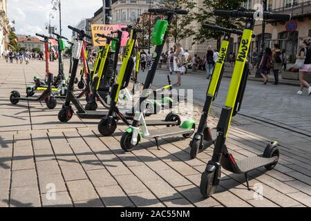 Many electric scooters, escooter or e-scooter of the ride sharing company HIve left on sidewalk in Warsaw, Poland - Stock Photo