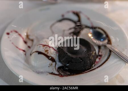 ice cream and chocolate filled fudgy lava cake on white plate - Stock Photo