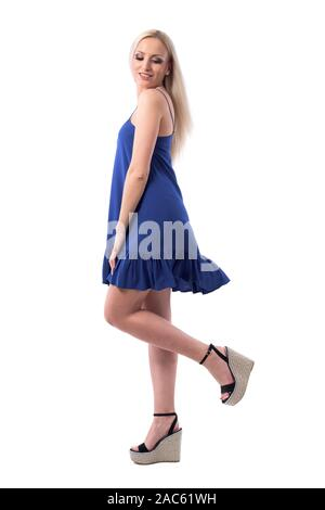 Side view of fresh young blonde carefree girl in summer blue dress posing with raised leg looking down. Full body isolated on white background. - Stock Photo