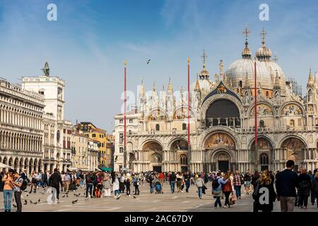 Piazza San Marco crowded with tourists in a sunny day with the Basilica and Cathedral (St. Mark the evangelist), Veneto, Italy, Europe - Stock Photo
