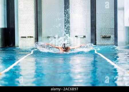 professional swimmer doing exercise in indoor swimming pool. - Stock Photo