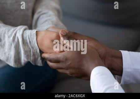 Young african american guy holding hands of woman, giving support. - Stock Photo