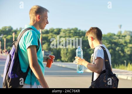 Young males drinking water on hot summer day, teenage boy talking holding bottle and can - Stock Photo