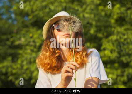 Summer outdoor portrait of romantic teenage girl in hat with big fluffy dandelion in nature, blowing on dry dandelion
