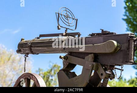 Old anti-aircraft machine gun in the background of the blue sky - Stock Photo