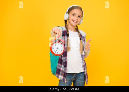 Beginning of lessons. Time go school. School time. Happy girl hold alarm clock counting minutes. Knowledge day. Classes schedule. Schoolgirl hold alarm clock yellow background. School timing concept. - Stock Photo