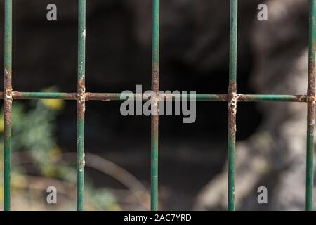 Wire mesh fence closeup photo. Green bush and huge cave in blurred background. Thin pillars. Decorative board front of garden. Building construction.