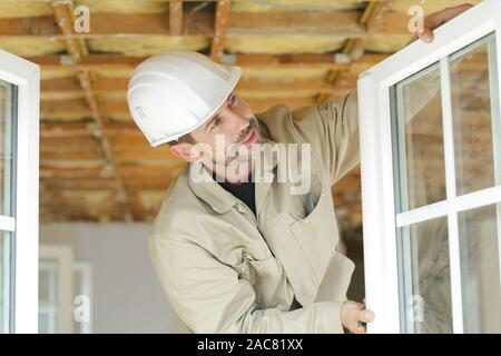 handsome man installing bay window - Stock Photo