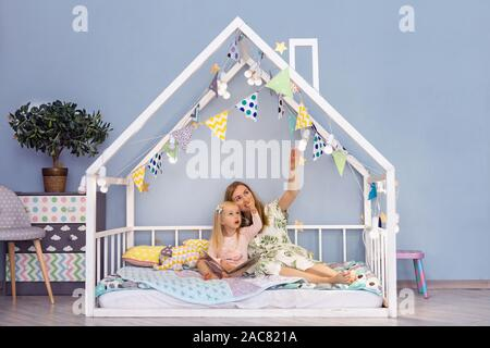 Happy young mother and her adorable daughter looking up and showing something interesting while sitting on bed