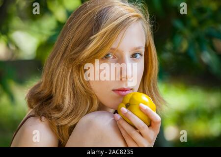 Headshot eyeshot country-girl with pear in hand pretty and beautiful young person charming charismatic gorgeous stunning photogenic appealing - Stock Photo