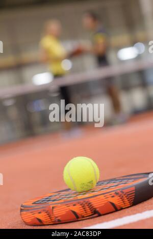 close-up of paddle tennis balls on blue turf in court - Stock Photo