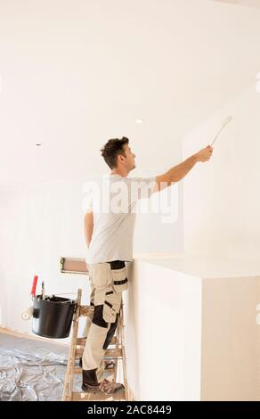 Shot of professional contractors standing on ladder and painting wall while refurbishing the apartment.