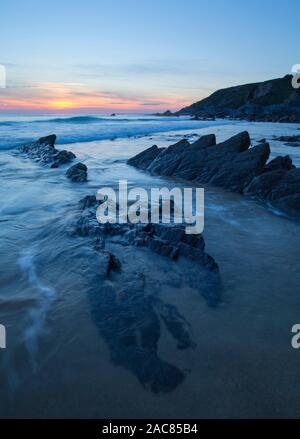 Sunset at Dollar Cove Gunwalloe on the Lizard Coast of Cornwall - Stock Photo