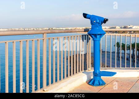 Telescope overlooking for city streets and sea shore from above - Stock Photo