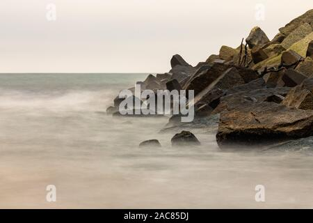 Stones laid on a breakwater in a sea port. The exhibition photographed with a long time. Autumn season. - Stock Photo