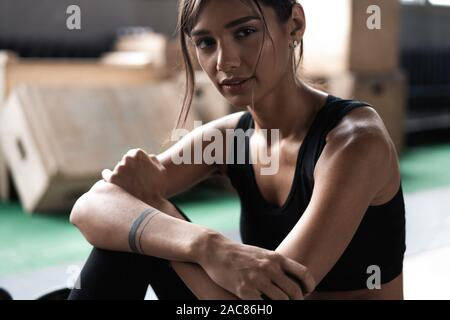 Young woman sitting on floor after her workout and looking down. Female athlete taking rest after fitness training - Stock Photo