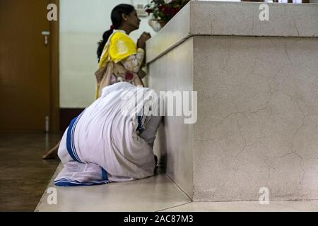 Mother Teresa sister praying at the tomb in the motherhouse located in Kolkata, India