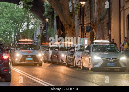 A line of taxis wait with their light on outside a building in Sydney in the early evening - Stock Photo