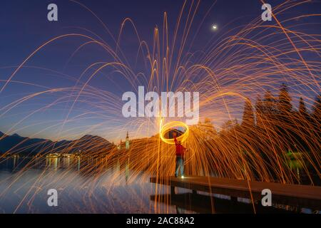 Steel wool shot over Bled Lake shore, early morning, blue hour, Slovenia, 2019. - Stock Photo
