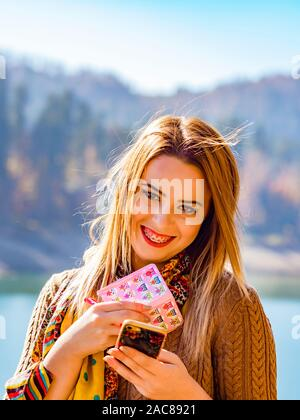 Young woman busy with small note paper notebook and smartphone in hands smiling with teeth braces giggling giggle - Stock Photo