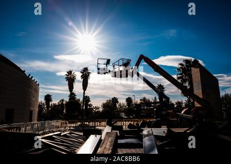 Valencia, Spain - November 26, 2019: Cranes with basket ready to repair some damage in a building, backlit. - Stock Photo