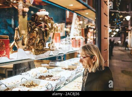 Strasbourg, France - Nov 23, 2017: Side view of French woman admiring diverse sweets chocolates and cakes in Christian bakery store in central Strasbourg - Stock Photo