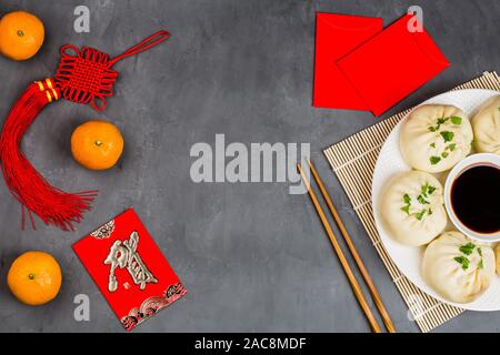Chinese New Year decoration with dumplings, tangerines, soy sauce, chopsticks, red envelopes on gray concrete background. Happy Chinese new year 2020 - Stock Photo