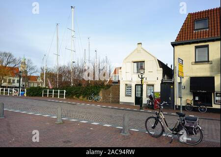 Enkhuizen, North Holland / Netherlands - March 05, 2012: Houses and bicycle on the road on a street of Enkhuizen city of Netherlands at sunny spring d - Stock Photo