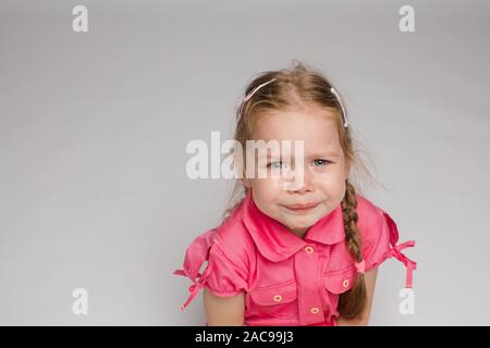 Little girl in pink shirt crying on isolated background - Stock Photo