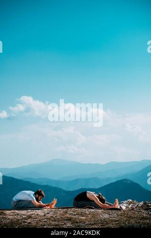 Find you balance, find yourself. Beautiful young couple doing acro yoga in nature - Stock Photo