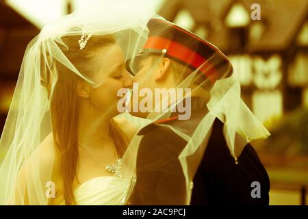 A young beautiful bride kisses her newly wed husband under a veil, after marrying her childhood sweetheart on their military wedding day - Stock Photo