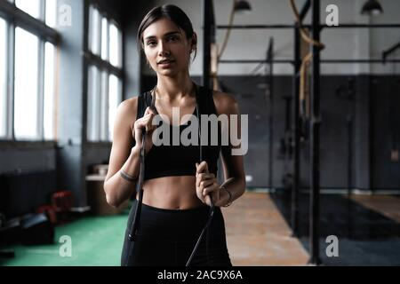 Fit and healthy woman standing at gym with skipping rope. Sportswoman resting after workout. - Stock Photo