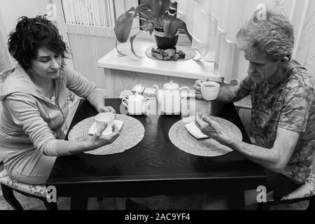 Black and white conceptual photo of an adult couple husband and wife during dinner and looking at the phones ignoring and not communicating with each - Stock Photo