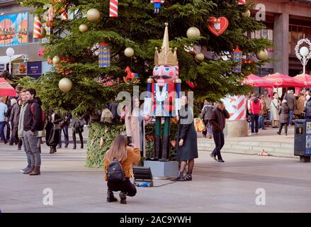 Two lovely ladies posing next to one of the Nutcracker statue next to large Christmas tree in centre square at Advent Market. Zagreb, Croatia - Stock Photo