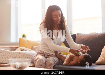 Warm toned portrait of caring African-American mother dressing her baby on couch against sunlight, copy space