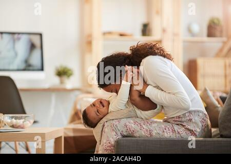 Side view portrait of caring African-American mother kissing cute baby boy while playing at home, copy space