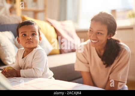 Smiling young mother sitting and playing with her little child on the sofa in the room