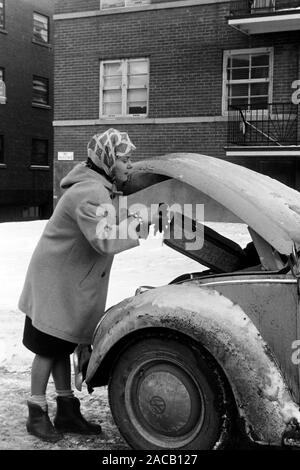 Frau macht den VW Käfer reisefertig, 1963. Woman packing and checking the VW Beetle before taking off, 1963. - Stock Photo