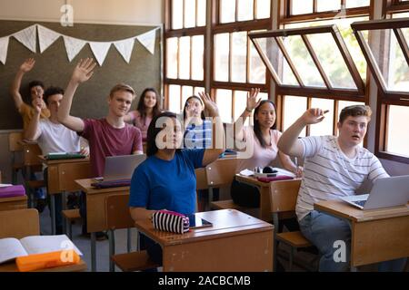 Teenagers in school classroom - Stock Photo