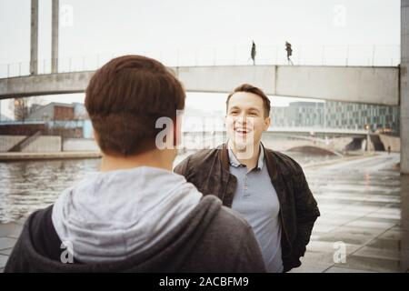 two male teenage friends having a fun conversation - lifestyle or city life concept - urban riverside location in Berlin Germany - Stock Photo