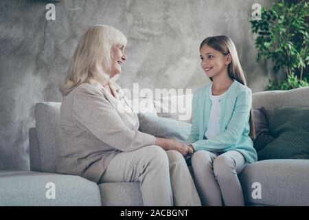 Photo of cheerful positive grandma with granddaughter first one teaching telling story her child wise living things sitting indoors on sofa - Stock Photo
