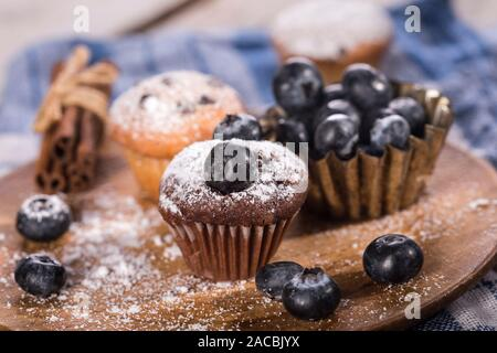 Blueberry and chocolate muffins on a wooden background. - Stock Photo